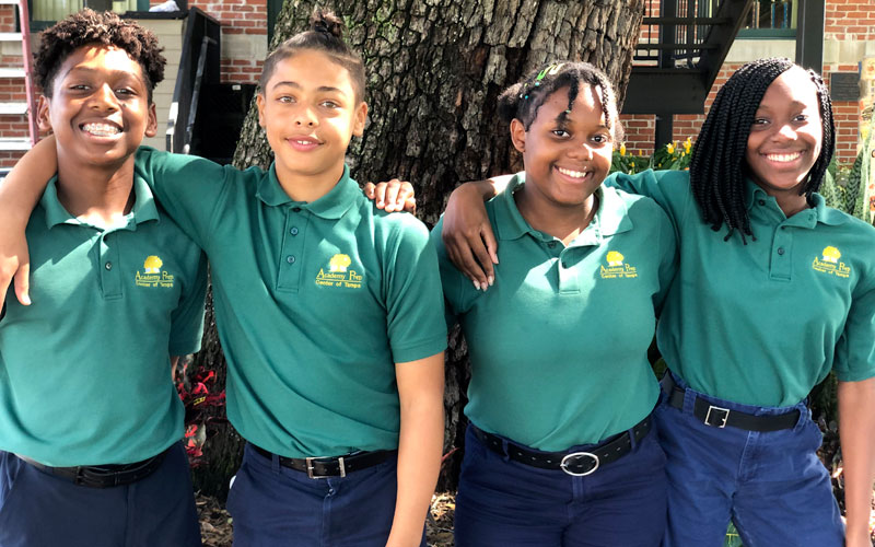 Photo of four students in green shirts.